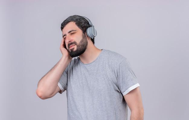 Erfreulicher junger hübscher mann, der kopfhörer trägt, die musik mit hand auf kopfhörer und geschlossenen augen lokalisiert auf weißer wand hören