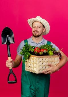 Erfreulicher junger hübscher slawischer gärtner in der uniform und im hut, die korb des gemüses und des spatens halten