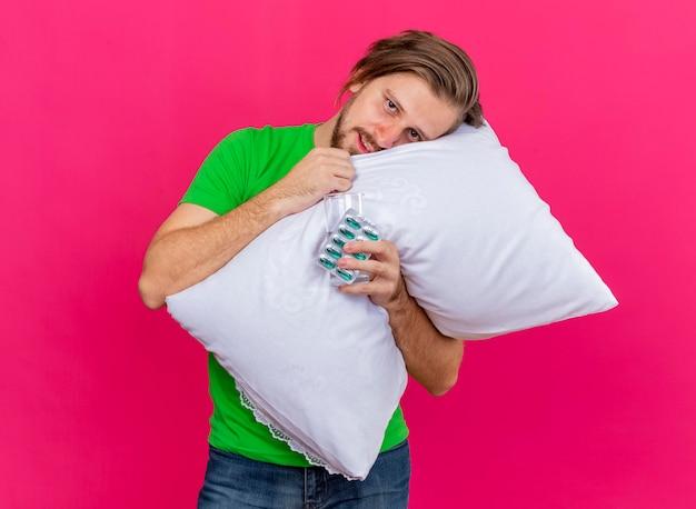 Erfreulicher junger hübscher slawischer kranker mann, der kissen umarmt, das kopf auf mit packung kapseln und glas wasser in der hand setzt, die front lokal auf rosa wand lokalisiert betrachtet