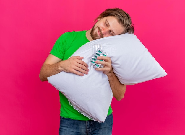 Erfreulicher junger hübscher slawischer kranker mann, der kissen umarmt, das kopf mit packung kapseln und glas wasser in der hand setzt, die wasser und kapseln lokalisiert auf rosa wand mit kopienraum betrachten
