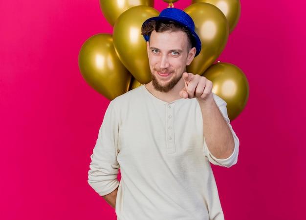Erfreulicher junger hübscher slawischer party-typ, der partyhut trägt, der ballons hinter seinem rücken hält und nach vorne zeigt, isoliert auf rosa wand mit kopienraum