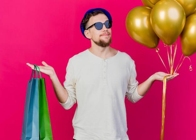 Erfreulicher junger hübscher slawischer party-typ, der partyhut und sonnenbrille hält, die luftballons und papiertüten halten, die front lokalisiert auf rosa wand betrachten