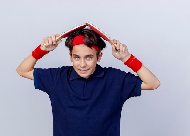Erfreulicher junger hübscher sportlicher junge, der stirnband und armbänder mit zahnspangen trägt, die kopf mit tischtennisschlägern berühren, die auf weißer wand lokalisiert werden