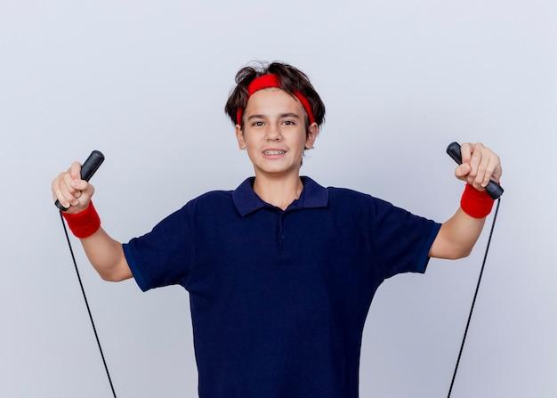 Erfreulicher junger hübscher sportlicher junge, der stirnband und armbänder mit zahnspangen trägt, die mit dem springseil trainieren, das an der front lokalisiert auf weißer wand betrachtet