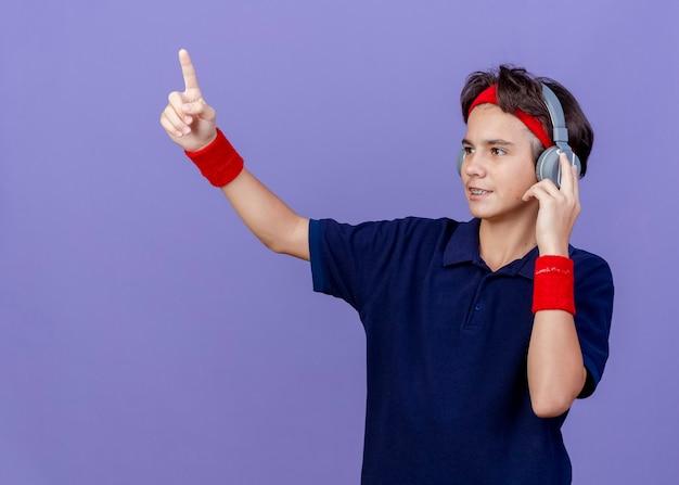 Erfreulicher junger hübscher sportlicher junge, der stirnband und armbänder und kopfhörer mit zahnspangen trägt, die seitenberührungskopfhörer betrachten, die lokal auf lila hintergrund mit kopienraum zeigen