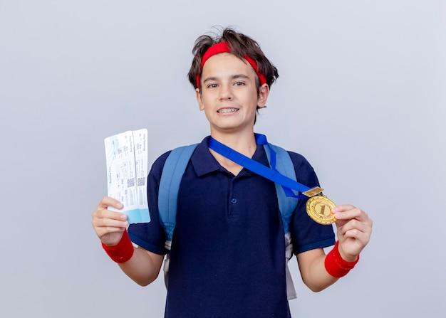 Erfreulicher junger hübscher sportlicher junge, der stirnband und armbänder und medaille um hals-rückentasche mit zahnspangen trägt, die kamera betrachten, die flugtickets und medaille lokalisiert auf weißem hintergrund hält
