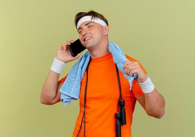 Erfreulicher junger hübscher sportlicher mann, der stirnband und armbänder mit handtuch und springseil um den hals trägt und am telefon spricht, das gerade schaut und handtuch lokalisiert auf olivgrüner wand hält
