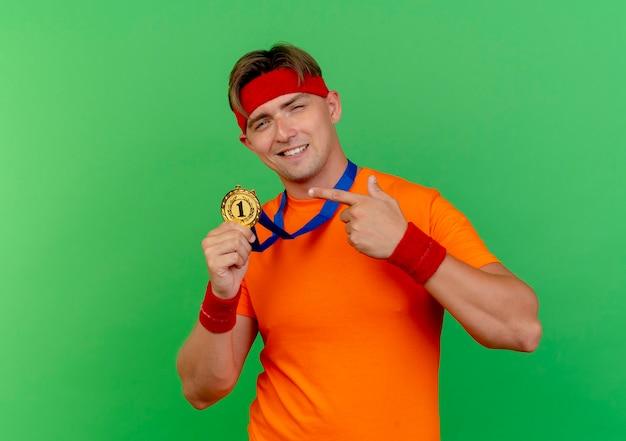 Erfreulicher junger hübscher sportlicher mann, der stirnband und armbänder mit medaille um hals hält und auf medaille zeigt, die auf grüner wand isoliert ist