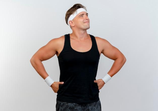 Erfreulicher junger hübscher sportlicher mann, der stirnband und armbänder trägt, die hände auf taille setzen und seite lokalisiert auf weißer wand betrachten