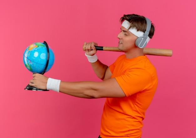 Erfreulicher junger hübscher sportlicher mann, der stirnband und armbänder und kopfhörer trägt, die in der profilansicht stehen und baseballschläger auf schulter und globus halten und globus lokalisiert auf rosa wand betrachten