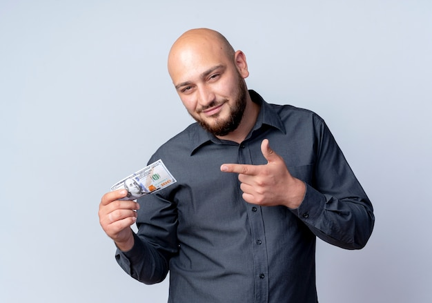 Erfreulicher junger kahlköpfiger callcenter-mann, der auf weißem hintergrund lokalisiertes geld hält und zeigt