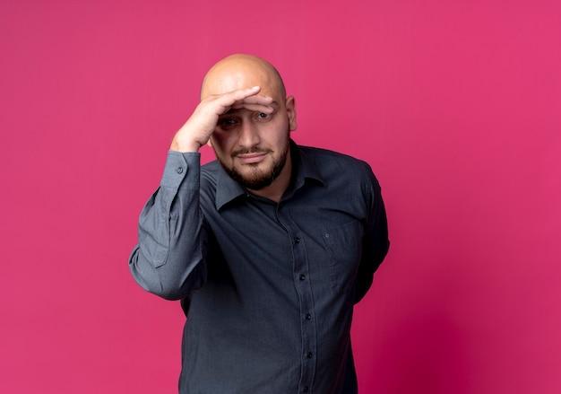 Erfreulicher junger kahlköpfiger callcenter-mann, der entfernung betrachtet und hand hinter rücken isoliert auf purpurrotem hintergrund mit kopienraum hält