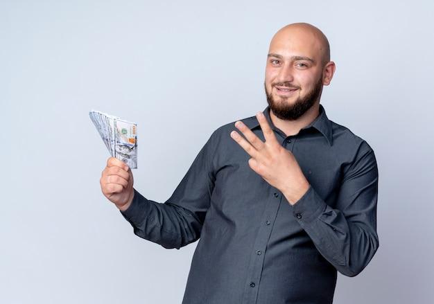 Erfreulicher junger kahlköpfiger callcenter-mann, der geld hält und drei lokalisiert auf weißem hintergrund zeigt