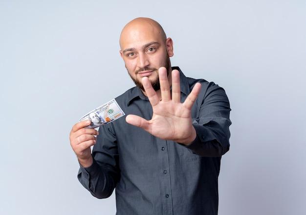 Erfreulicher junger kahlköpfiger callcenter-mann, der geld hält und hand in richtung kamera streckt lokalisiert auf weißem hintergrund