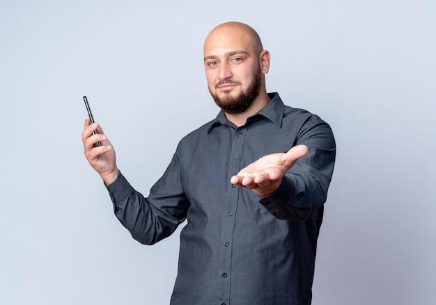 Erfreulicher junger kahlköpfiger callcenter-mann, der handy hält und hand an kamera lokalisiert auf weißem hintergrund mit kopienraum ausdehnt