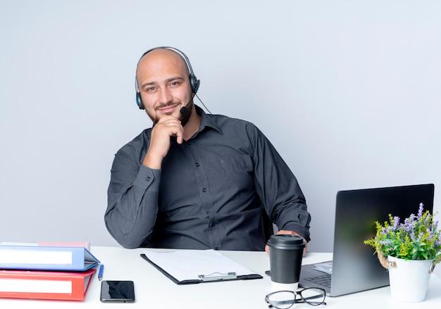 Erfreulicher junger kahlköpfiger callcenter-mann, der headset trägt, das am schreibtisch mit arbeitswerkzeugen sitzt, die hand auf kinn lokalisiert auf weißem hintergrund setzen