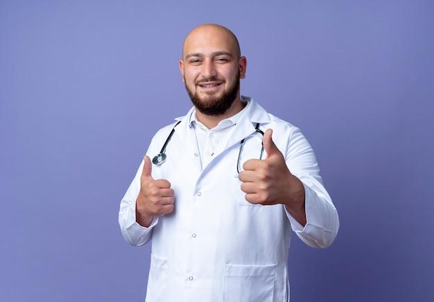 Erfreulicher junger kahlköpfiger männlicher arzt, der medizinische robe trägt und seinen daumen oben auf blauem hintergrund stethoskopiert