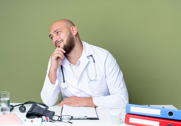 Erfreulicher junger kahlköpfiger männlicher arzt, der medizinische robe und stethoskop trägt, die am schreibtisch arbeiten, mit medizinischen werkzeugen, die hand auf kinn lokalisiert auf grünem hintergrund setzen