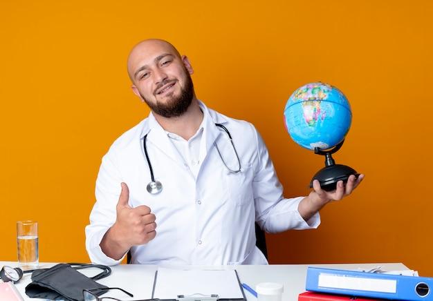 Erfreulicher junger kahlköpfiger männlicher arzt, der medizinische robe und stethoskop trägt, die am schreibtisch mit medizinischen werkzeugen sitzen, die globus seinen daumen oben auf orange hintergrund lokalisiert halten