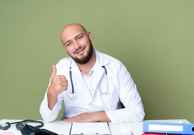 Erfreulicher junger kahlköpfiger männlicher arzt, der medizinische robe und stethoskop trägt, die am schreibtisch sitzen, arbeiten mit medizinischen werkzeugen seinen daumen oben lokalisiert auf grünem hintergrund