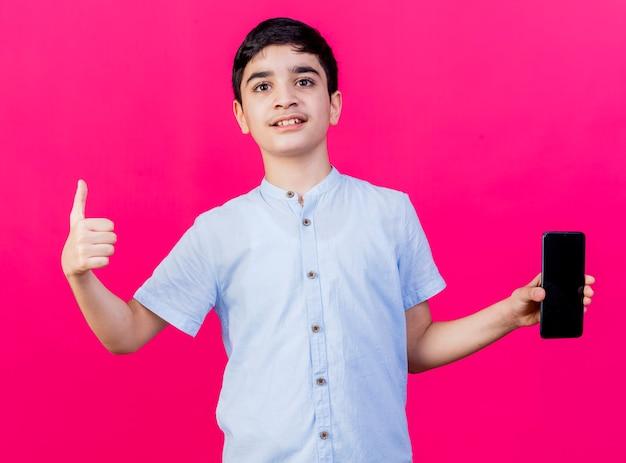 Erfreulicher junger kaukasischer junge, der handy zeigt kamera zeigt daumen oben isoliert auf purpurrotem hintergrund