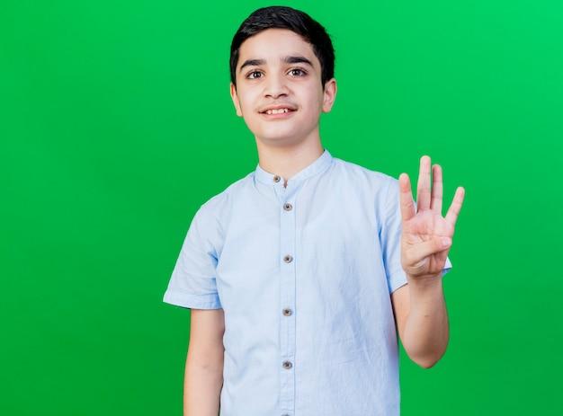 Erfreulicher junger kaukasischer junge, der kamera betrachtet, die vier mit hand lokalisiert auf grünem hintergrund mit kopienraum zeigt