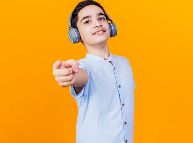Erfreulicher junger kaukasischer junge, der kopfhörer trägt und auf kamera zeigt, die auf orange hintergrund mit kopienraum lokalisiert ist