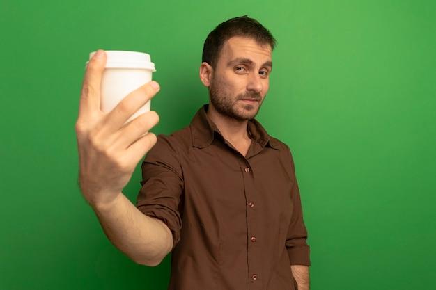 Erfreulicher junger kaukasischer mann, der plastikkaffeetasse in richtung kamera ausdehnt, die kamera lokalisiert auf grünem hintergrund mit kopienraum betrachtet