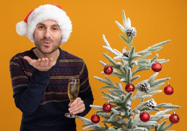 Erfreulicher junger kaukasischer mann, der weihnachtshut trägt, der nahe verziertem weihnachtsbaum hält, der glas champagner hält, der kamera schaut, die schlagkuss lokalisiert auf orange hintergrund sendet