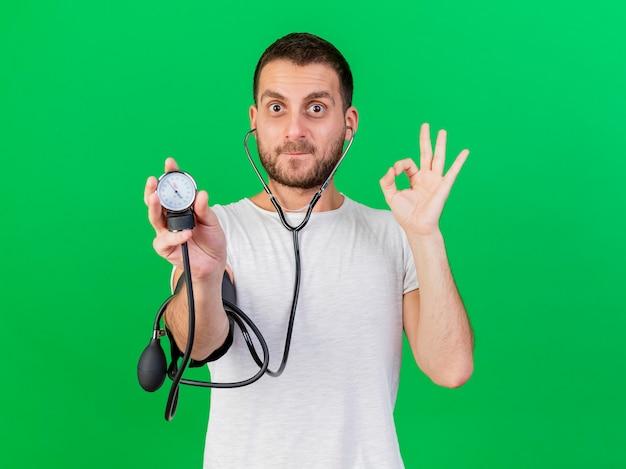 Erfreulicher junger kranker mann, der stethoskop trägt und seinen eigenen druck mit blutdruckmessgerät misst, das auf grünem hintergrund isoliert wird