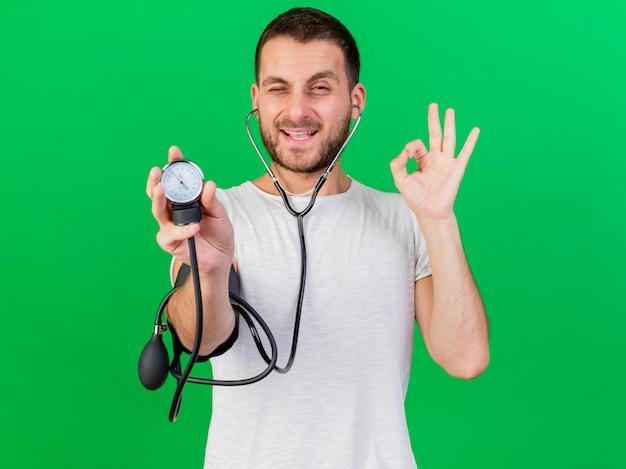 Erfreulicher junger kranker mann, der stethoskop trägt und seinen eigenen druck mit blutdruckmessgerät misst, das okey geste lokalisiert auf grünem hintergrund zeigt
