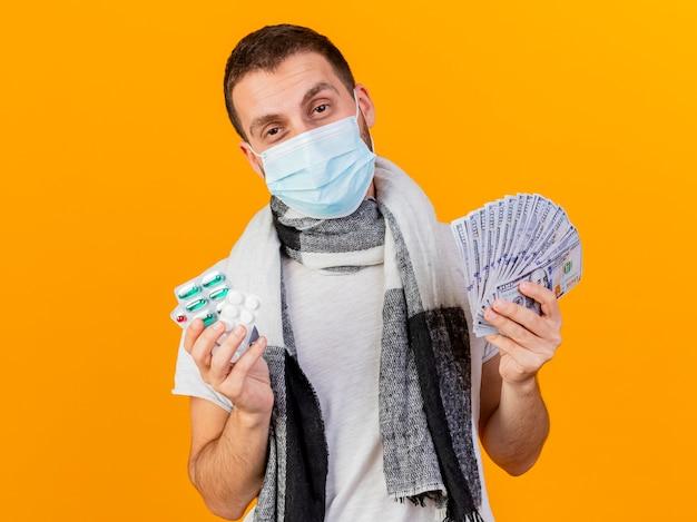Erfreulicher junger kranker mann, der wintermütze und medizinische maske hält, die pillen und bargeld auf gelbem hintergrund hält