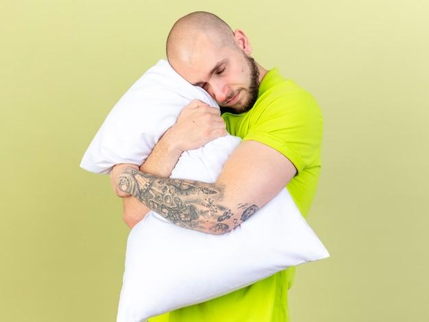 Erfreulicher junger kranker mann umarmt kissen lokalisiert auf olivgrüner wand