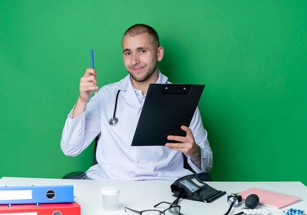 Erfreulicher junger männlicher arzt, der medizinische robe und stethoskop trägt, sitzt am schreibtisch mit arbeitswerkzeugen, die klemmbrett und stift lokalisiert auf grüner wand halten