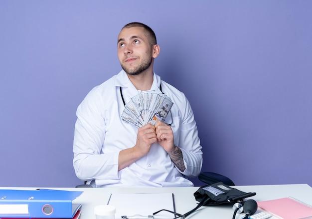 Erfreulicher junger männlicher arzt, der medizinisches gewand und stethoskop trägt, sitzt am schreibtisch mit arbeitswerkzeugen, die geld halten und lokalisiert auf lila wand suchen