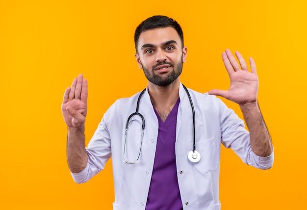 Erfreulicher junger männlicher arzt, der medizinisches stethoskopkleid trägt, das verschiedene zahlen auf lokalisiertem gelbem hintergrund zeigt