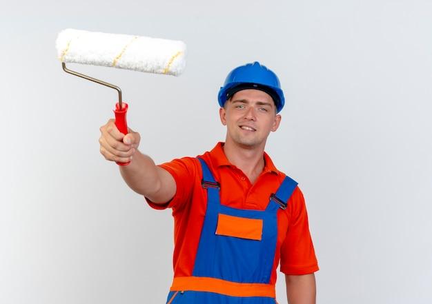 Erfreulicher junger männlicher baumeister, der uniform und sicherheitshelm trägt, der farbroller isoliert auf weißer wand heraushält