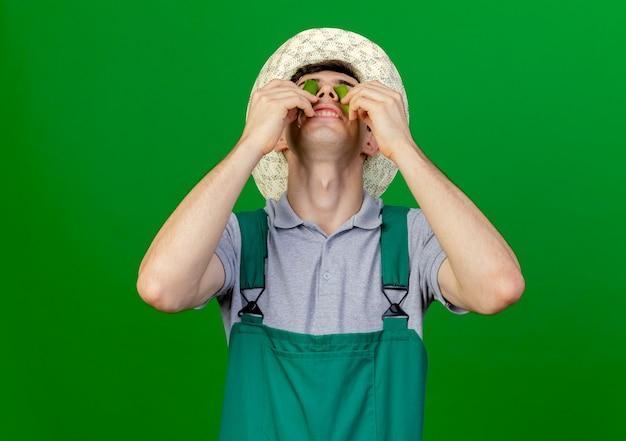 Erfreulicher junger männlicher gärtner, der gartenhut trägt, bedeckt augen mit gebrochenem heißem pfeffer lokalisiert auf grünem hintergrund mit kopienraum