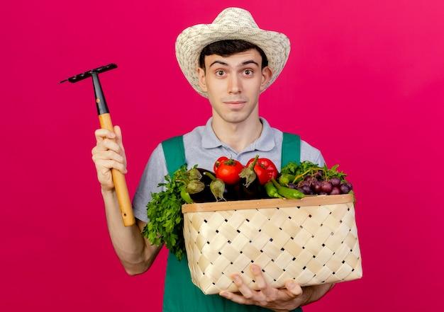 Erfreulicher junger männlicher gärtner, der gartenhut trägt, hält gemüsekorb und rechen