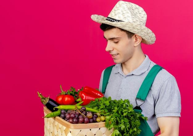 Erfreulicher junger männlicher gärtner, der gartenhut trägt, hält und schaut auf gemüsekorb