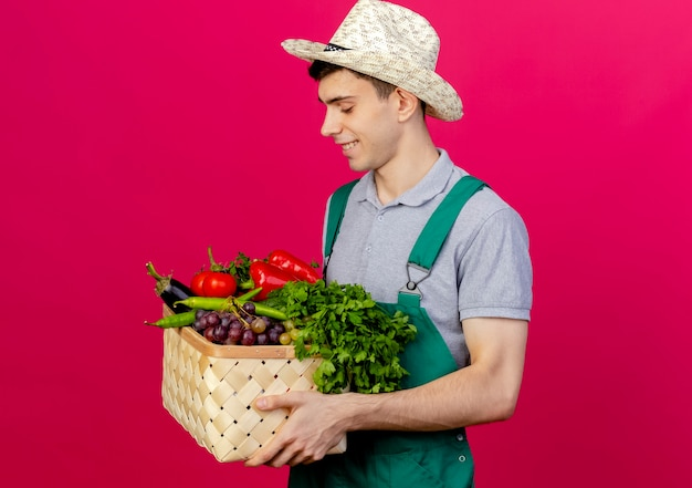 Erfreulicher junger männlicher gärtner, der gartenhut trägt, steht seitlich haltend und betrachtet gemüsekorb