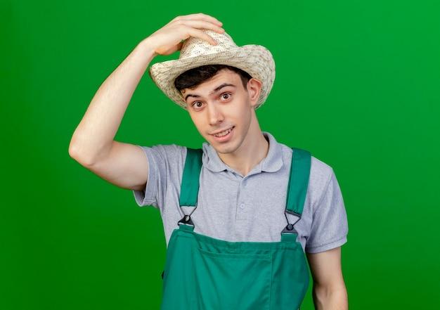 Erfreulicher junger männlicher gärtner, der gartenhut trägt und hält