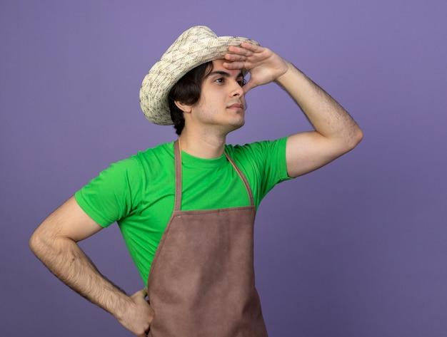 Erfreulicher junger männlicher gärtner in der uniform, die gartenhut trägt, der abstand mit der hand betrachtet