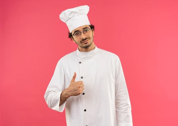 Erfreulicher junger männlicher koch, der kochuniform trägt und seinen daumen auf rosa wand lokalisiert