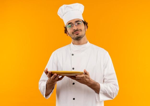 Erfreulicher junger männlicher koch, der kochuniform und brille hält, die platte auf gelber wand isoliert hält