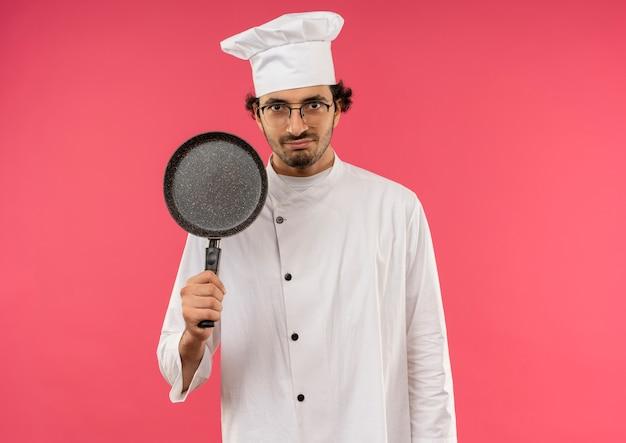 Erfreulicher junger männlicher koch, der kochuniform und gläser trägt, die bratpfanne auf rosa halten