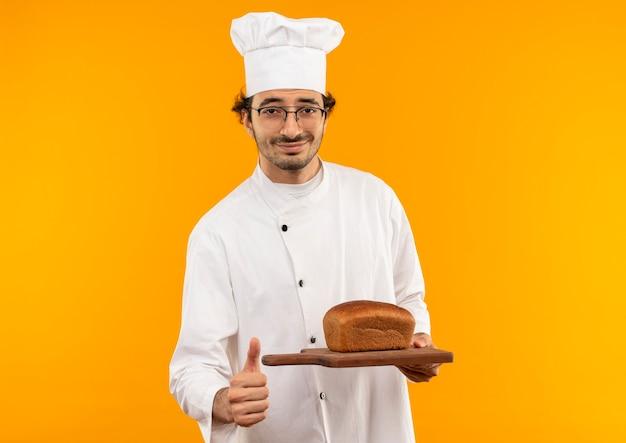 Erfreulicher junger männlicher koch, der kochuniform und gläser trägt, die brot auf schneidebrett halten, lokalisiert auf gelber wand