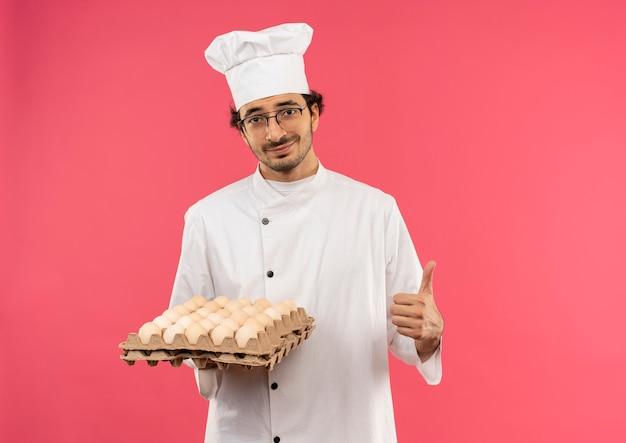 Erfreulicher junger männlicher koch, der kochuniform und gläser trägt, die charge von eiern halten, sein daumen oben isoliert auf rosa wand