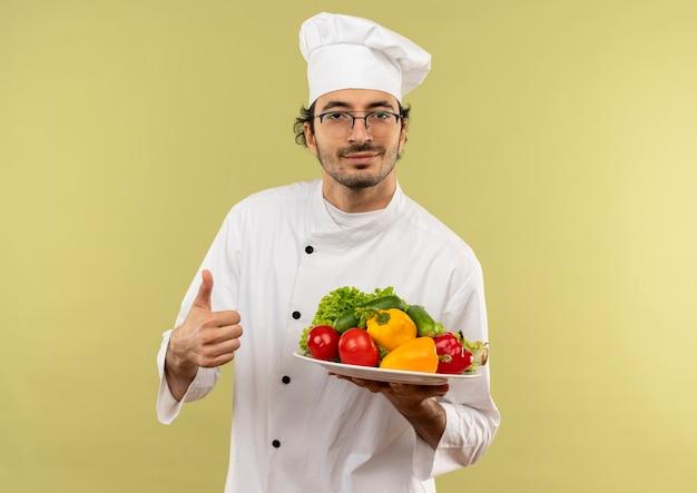 Erfreulicher junger männlicher koch, der kochuniform und gläser trägt, die gemüse auf teller halten, sein daumen oben lokalisiert auf grüner wand