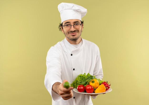 Erfreulicher junger männlicher koch, der kochuniform und gläser trägt, die gemüse auf teller halten und gurke lokalisiert auf grüner wand halten